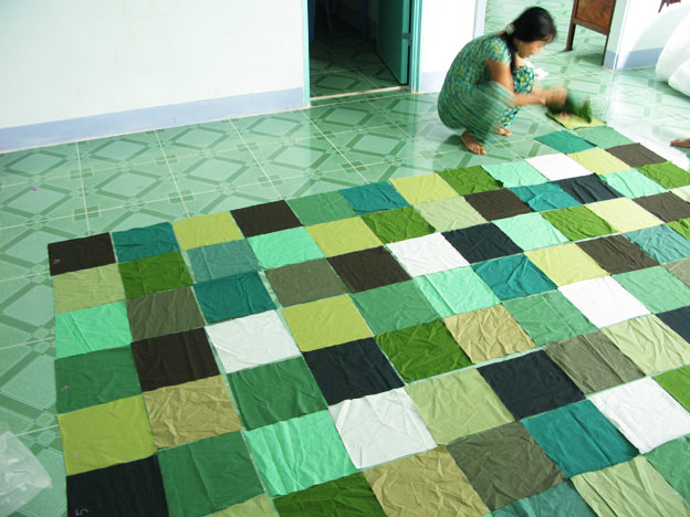Squares of green cotton being lined up to prepare for the patchwork of a king size bed quilt
