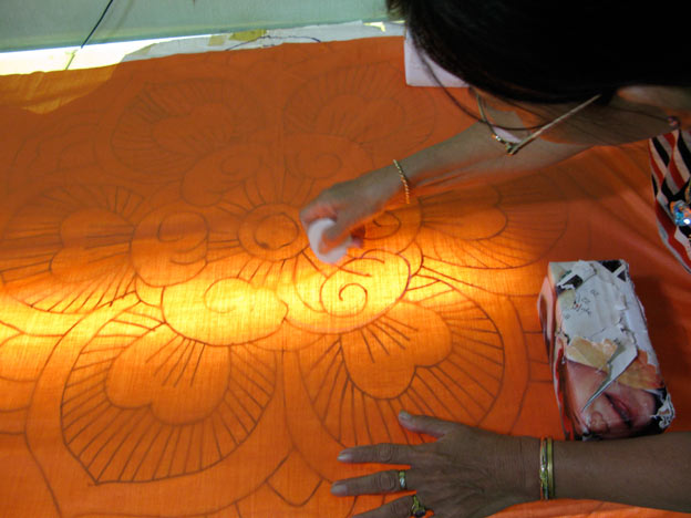 The design on paper is traced on the fabric on a home made glass and neon lighting table